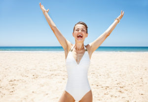 Happy woman in a white swimsuit on a sandy beach