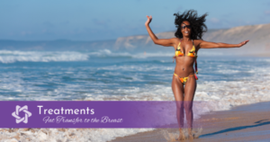 Happy woman on beach with arms stretched out splashing along the shore
