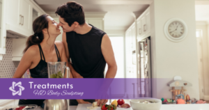 Young, healthy couple kissing in kitchen while making healthy smoothie